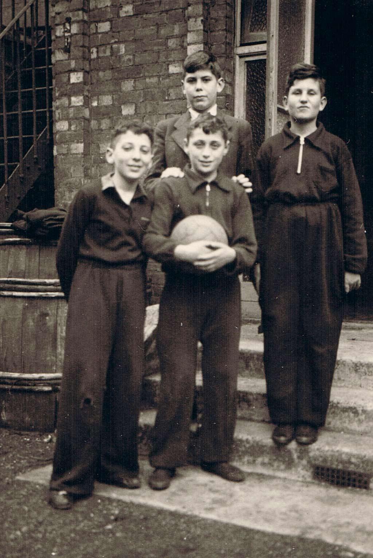 Ernst Kohlmann (Ernest Kolman), Julius Weil, Fritz Penas (Fred Marchand) (v.l.n.r.) und Hans Walter (hinten) vor dem Hostel in London, Minster Road 1, mit einem vom FC Arsenal geschenkten Fußball, 1939